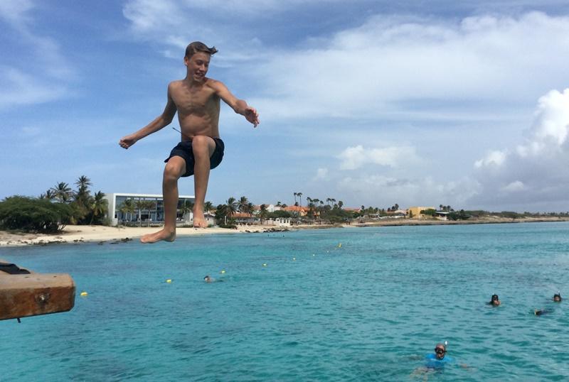 Boy jumping into sea Aruba