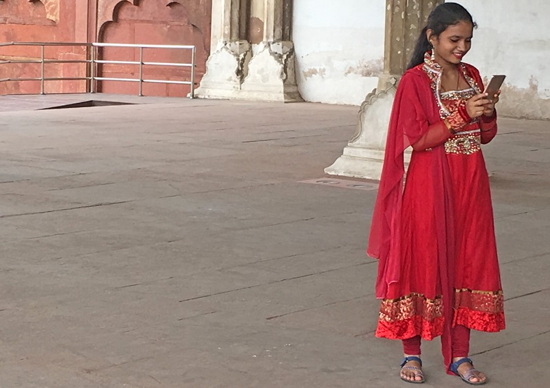 Girl in red sari with mobile phone at Red Fort, Agra, in Rajashtan India - photo Zoe Dawes