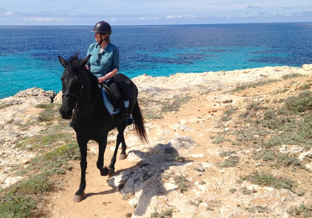 Admiring the view on horse at Son Bou Cami de Cavalls Menorca