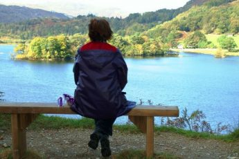The Quirky Traveller on bench at Rydal Water in the Lake District, Cumbria