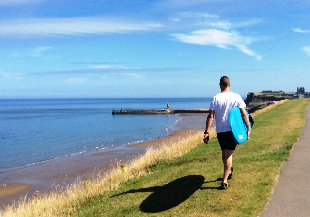 Surfer walking along Whitby Cliffs, North Yorkshire - zoedawes